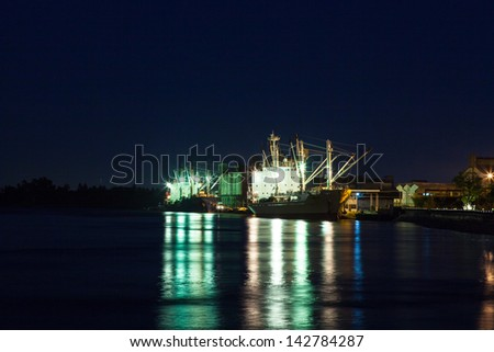 Shipping port at night. Cargo ship to dock at night. - stock photo