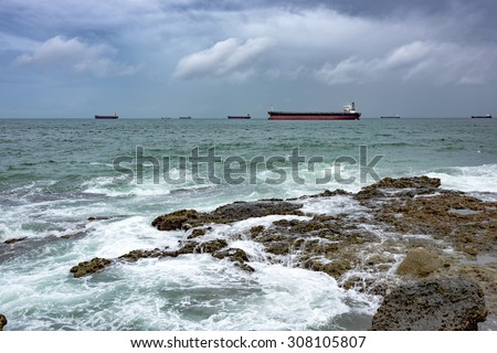 Ships anchored in the All Saints bay in Salvador during bad weather waiting to moor in the harbor. - stock photo