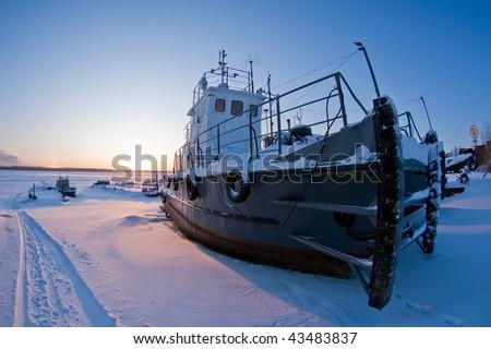 Ships covered with snow on coast Ob River, await  season of navigation. winter sunset, Siberia, Surgut city. - stock photo