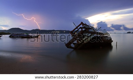 shipwreck and Lightning over sea at dawn in Phuket. Thailand - stock photo