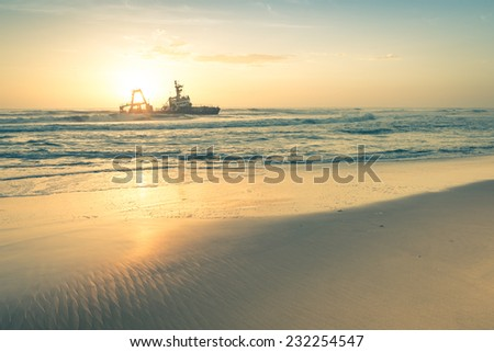 Shipwreck at sunset on the namibian Skeleton Coast - Nature wonders of Africa in Namibia west territory - stock photo