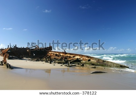 shipwreck in sand and surf at beach - Maheno Wreck, Fraser Island, Australia - stock photo