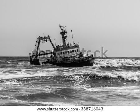 Shipwreck on Skeleton Coast of Atlantic Ocean in Namibia. Black and white image. - stock photo