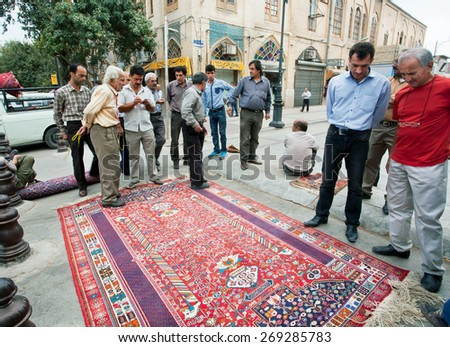 SHIRAZ, IRAN - OCT 21: Crowd of men talking about ancient carpet near the Persian rugs market on October 21, 2014. With population of 1,500,000, Shiraz is one of the oldest cities of ancient Persia.  - stock photo