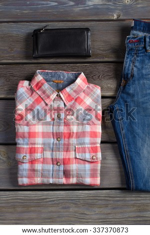 Shirt, jeans and a leather purse on a wooden board. - stock photo
