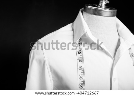 Shirt on mannequin with white measurement tape - stock photo