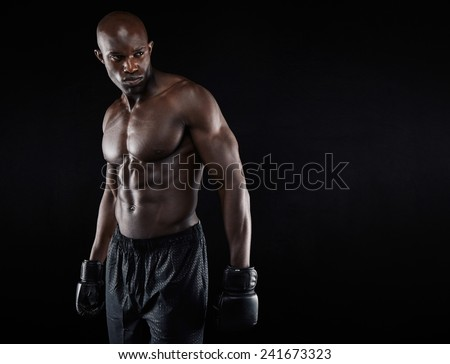 Shirtless african boxer looking away on black background. Young man wearing boxing gloves looking at copy space. - stock photo