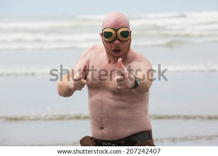 Shirtless bald man wearing aviator goggles at the beach - stock photo