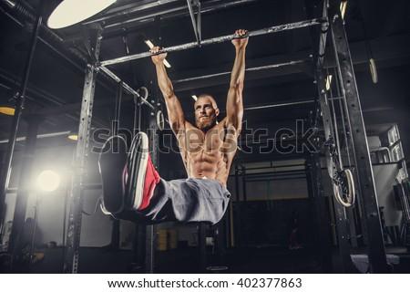 Shirtless bearded man doing stomach exercises on a horizontal bar. - stock photo