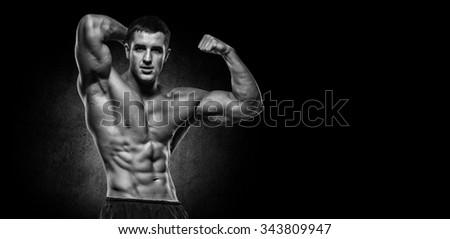 Shirtless bodybuilder holding dumbell and showing his muscular arms. - stock photo