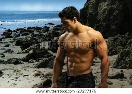 Shirtless bodybuilder on the beach with rocks and ocean - stock photo