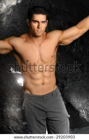 Shirtless bodybuilder with arms extended - stock photo