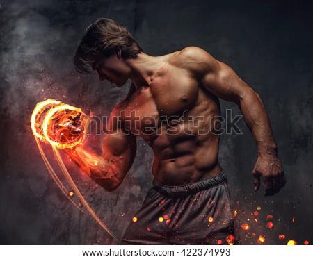 Shirtless bodybuilder with burning dumbbell. - stock photo