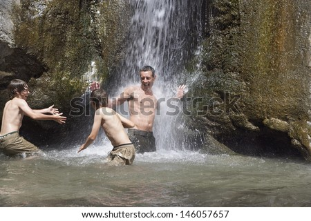 Shirtless father with two sons playing under waterfall - stock photo