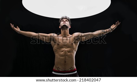 Shirtless handsome fit young man with arms spread open, light above him at studio - stock photo