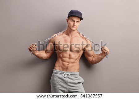 Shirtless male gangster holding a metal chain and leaning against a gray wall - stock photo