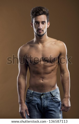 Shirtless male model posing over a brown background - stock photo