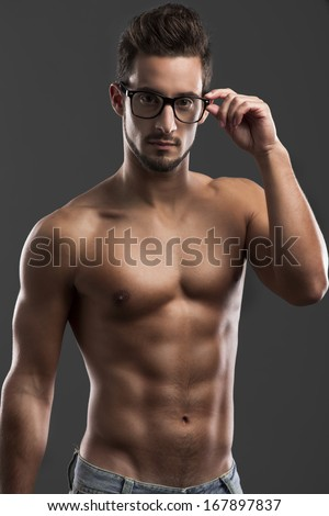 Shirtless male model posing with glasses over a gray background - stock photo