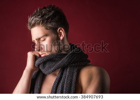 Shirtless male model wearing a scarf - Young handsome man against a dark red background - stock photo