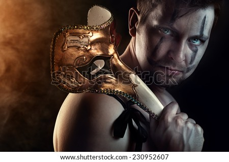 Shirtless man dancer or actor with creepy, scary mask on dark smoky background - stock photo