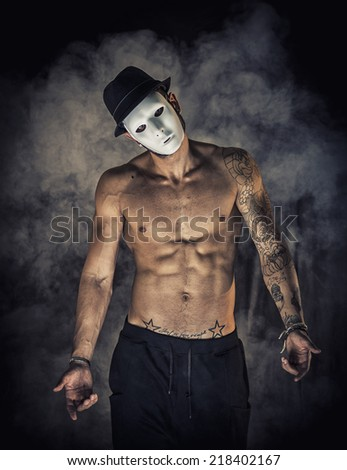Shirtless man dancer or actor with creepy, scary mask on tilted head, on dark smoky background - stock photo