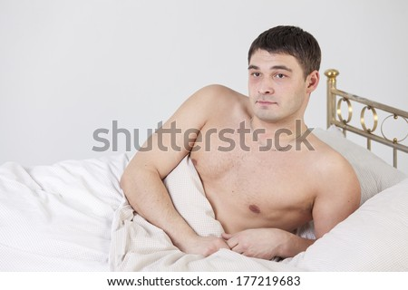 Shirtless man on the bed - shot in studio - stock photo