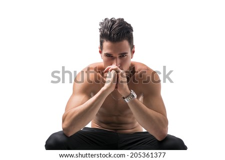 Shirtless man sitting deep in contemplation with his head to his hands staring straight ahead in a reverie, isolated on white - stock photo
