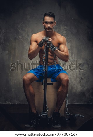 Shirtless man sitting on a wooden box and holding a hammer and chain. - stock photo