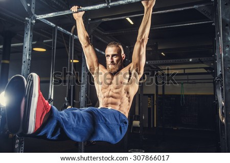 Shirtless man with deard in blue pants doing exersices on horizontal bar in a gym. - stock photo