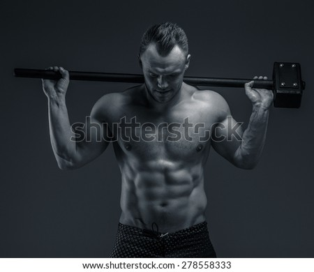 Shirtless muscular guy holding hummer. Isolated on grey background - stock photo