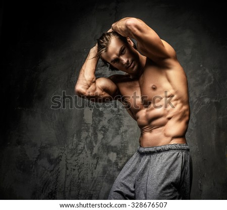Shirtless muscular guy posing in studio and showing his great torso. - stock photo