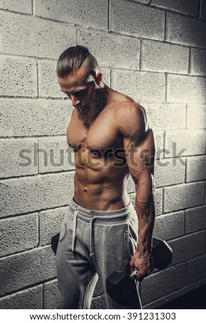 Shirtless muscular man doing biceps exercises with dumbbells. - stock photo