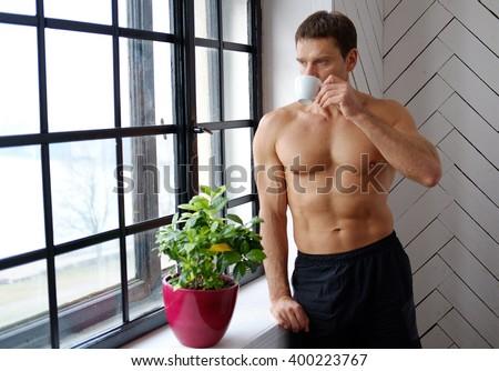 Shirtless muscular man drinking coffee. - stock photo