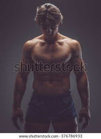 Shirtless muscular man in a shorts posing in deep shadow. - stock photo