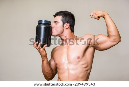 Shirtless muscular man kissing nutritional supplement over white background - stock photo