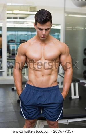 Shirtless muscular man looking down in gym - stock photo