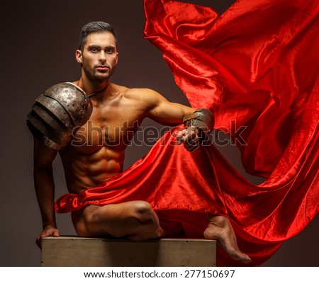 Shirtless muscular man sitting on a podium. Red cloth on grey background - stock photo