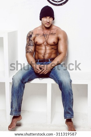 Shirtless muscular man with tatooes in blue jeans sitting on square podium over white wall. - stock photo