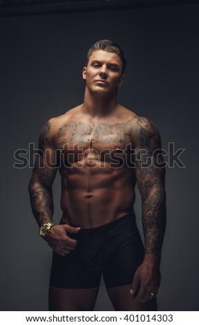 Shirtless muscular tattooed man posing in a deep shadows. - stock photo