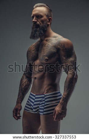 Shirtless muscular tattooed man with beard posing in shadow over grey background. - stock photo