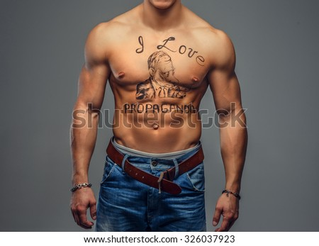 Shirtless muscular young guy with text on his torso. Isolated on grey torso. - stock photo