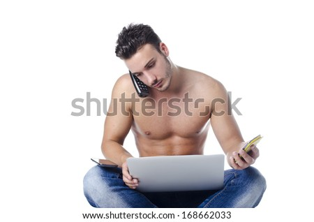 Shirtless muscular young man overwhelmed by technology, using laptop computer, PC tablet, phones - stock photo