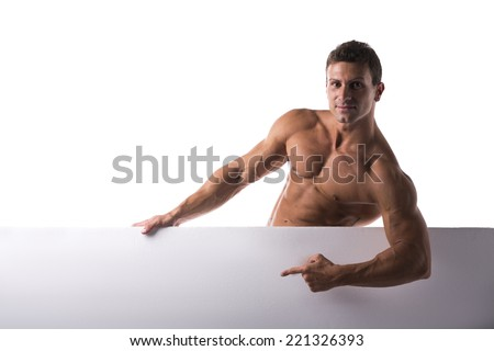 Shirtless muscular young man standing holding a blank horizontal white banner pointing finger at the copyspace for your text, on white - stock photo