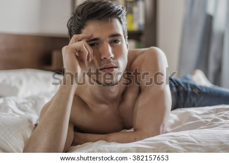 Shirtless sexy male model lying alone on his bed in his bedroom, looking at camera with a seductive attitude - stock photo