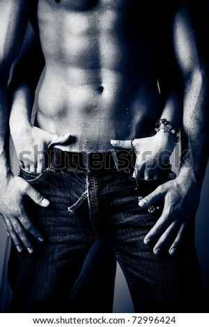 shirtless wet muscular man in jeans and woman hands, studio shot - stock photo