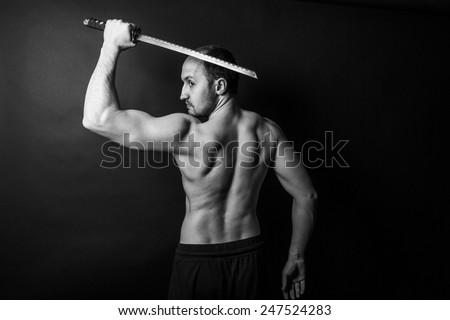 shirtless young man posing with katana sword - stock photo