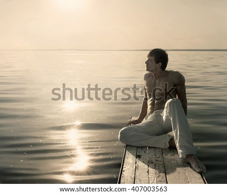 Shirtless young man sitting on small wooden jetty at summer sunny day - stock photo