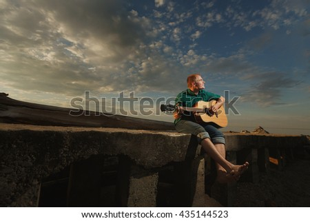 Shirtless young man wearing sunglasses, sitting on a pier and playing a guitar and smiling. Horizontal shot. - stock photo