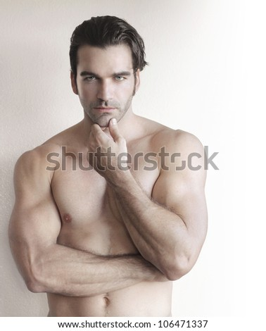 Shirtless young man with hand to chin against neutral background - stock photo