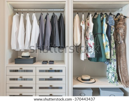 shirts and dress hanging on rail in wooden wardrobe at home - stock photo